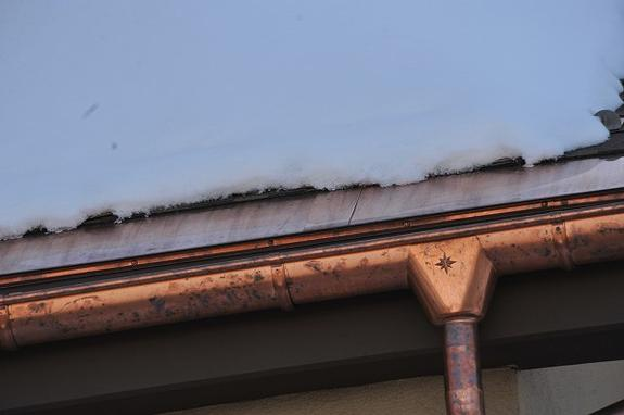 In this photo you can see how a simple single heat cable run pressed directly against a metal edge is able to prevent all icicle and ice dam formations. In addition, notice the 4 inch wide low profile transition panel used between two HotShingle panels. Clearly a very low profile solution to roof ice problems where they begin; the edge!