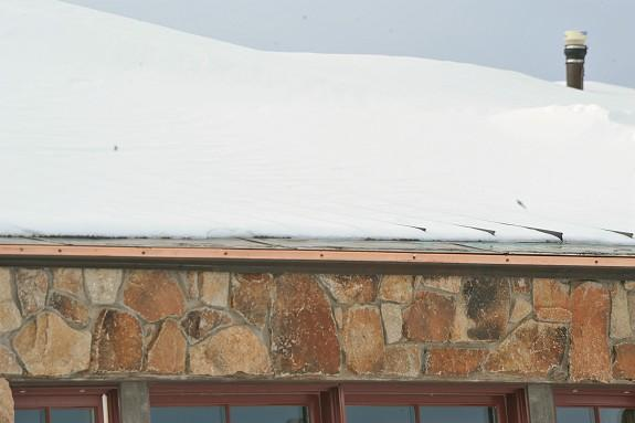 Although it is early in the winter season at this location which annually receives 300 inches of snowfall @ 11,200 foot elevation, it is clear to see how the only UL Listed metal roof edge ice melt system in America performs to prevent ice dams and icicles from forming on roof edges. The newly installed HotEdge Rail can be easily seen in this photo as it is still the shiny copper rail mounted directly below the existing metal drip edge on this copper roof. No modifications were necessary to the roof deck to install the HotEdge Rail, hence, installation costs are kept to a minimum.