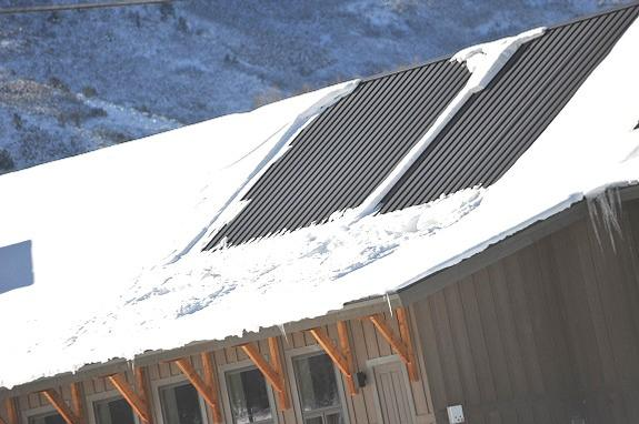 Changes in roof pitch on a metal roof often cause ice dams to develop. As you see in the photo, a steeper pitch upper roof transitions into a lower pitch roof causing snow pack to pile up where it becomes prisoner to freeze and thaw cycles and ice dams form. To prevent problematic ice dams from forming is necessary to install a system that will aggressively encourage piled snow pack to quickly melt. The patented HotSeam system (see photo insert) was designed to eliminate snow pack on all problematic areas on a metal roof structure.