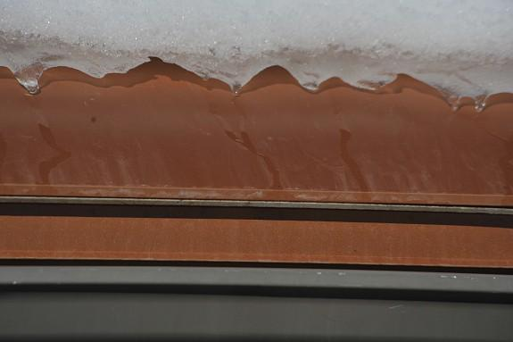 This photo shows HotShingle performing on an asphalt roof structure in high snow load region (300+ inches of snowfall on average each year). The HotShingle system easily retrofits to most asphalts shingle roofs. The HotEdge Rail is mounted below the HotShingle to firmly press heat tape against the HotShingle metal edge to transfer sufficient heat to prevent costly and dangerous ice dam and icicle formations.