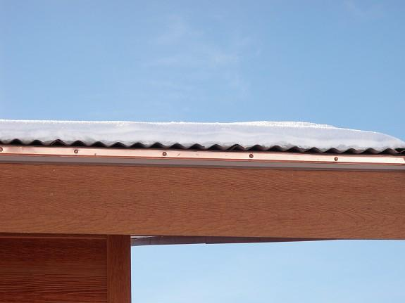 Even though the HotEdge containment and heat transfer system is not able to maintain continuous contact on a corrugated metal roof edge, it is enough heat transfer to prevent dangerous icicle formations. Dangerous icicles use to be a problem on this corrugated roof edge close to the front door on parking area at this mountain home.