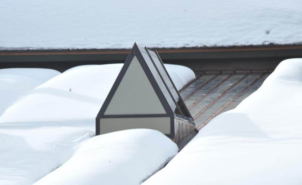 This location is a very high snowload region of the Rocky Mountains. Historically, snowpack/ice would build behind the dormer and significant damage would result during freeze and thaw cycles to the back side of the dormer. To prevent repeat performances, the HotSeam system was installed. As seen in this photo, it is possible to eliminate 100% of snow/ice build-up in problematic regions on any roof structure.