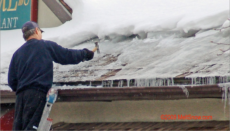 man removing ice from roof
